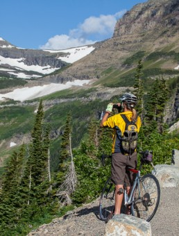 Bicyclist making a photograph at Glacier National Park